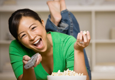 Happy woman laying on floor with bowl of popcorn, remote control